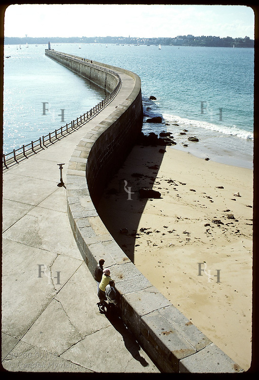 Elevated view of Mole des Noires pier with three tourists gazing toward beach at Saint Malo. France