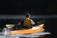 A man paddling a sea kayak