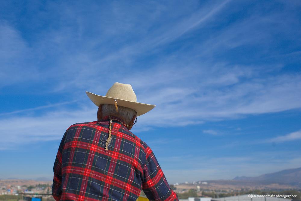 A man in a sombrero or cowboy hat crosses a bridge on a sunny day in Leon, Mexico near San Miguel de Allende.