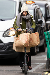 © Licensed to London News Pictures. 02/12/2020. London, UK. A shopper carries bags of purchases on an electric scooter on Regent Street. Today England returns to tiered COVID restrictions following the end of the second national lockdown. Photo credit: George Cracknell Wright/LNP
