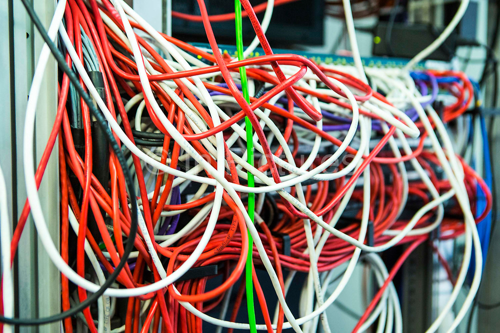 A large mass of multi-colored computer cables in a server room in a British business office in London, United Kingdom.