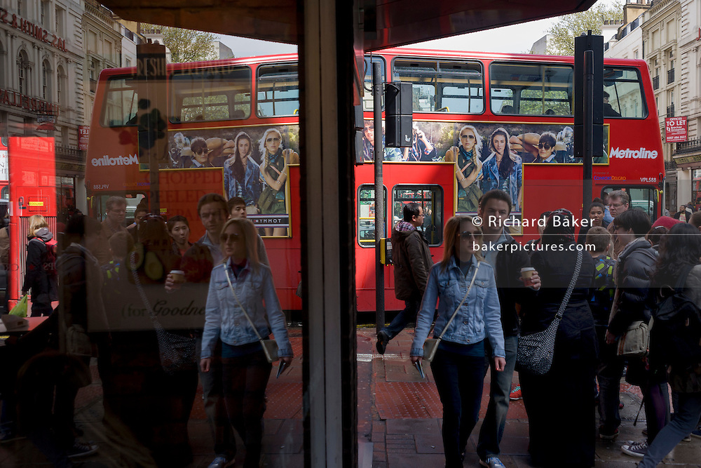 A stationary London bus is held in heavy traffic during central London disruption near Londoners and tourists.