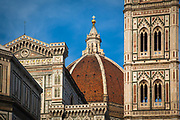 The Basilica di Santa Maria del Fiore is the cathedral church of Florence, Italy. The Duomo, as it is ordinarily called, was begun in 1296 in the Gothic style to the design of Arnolfo di Cambio and completed structurally in 1436 with the dome engineered by Filippo Brunelleschi. The exterior of the basilica is faced with polychrome marble panels in various shades of green and pink bordered by white and has an elaborate 19th century Gothic Revival façade by Emilio De Fabris.<br /> <br /> The cathedral complex, located in Piazza del Duomo, includes the Baptistery and Giotto's Campanile. The three buildings are part of the UNESCO World Heritage Site covering the historic centre of Florence and are a major attraction to tourists visiting the region of Tuscany. The basilica is one of Italy's largest churches, and until development of new structural materials in the modern era, the dome was the largest in the world. It remains the largest brick dome ever constructed.<br /> <br /> The cathedral is the mother church of the Roman Catholic Archdiocese of Florence, whose archbishop is currently Giuseppe Betori.