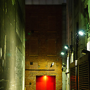 Red door in an alleyway in Montreal at night.