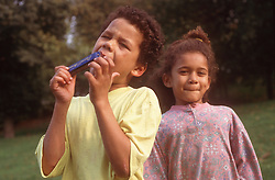 Brother and sister in park; boy playing mouth organ,