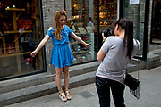 Model being photographed front and back for a clothing website on Yandaixiejie Street (meaning Tobacco Pipe Lane) in Beijing, China. Located near to Houhai in downtown Beijing, Yandai Xiejie Street is a Hutong which attracts many tourists at day and night to it's souvenir shops and towards the bar area it leads to.