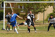 The undefeated Deportivo Colomex (Black) defend against a Team Shlama F.C. scoring opportunity (Blue) during National Soccer League play in Skokie, Il.