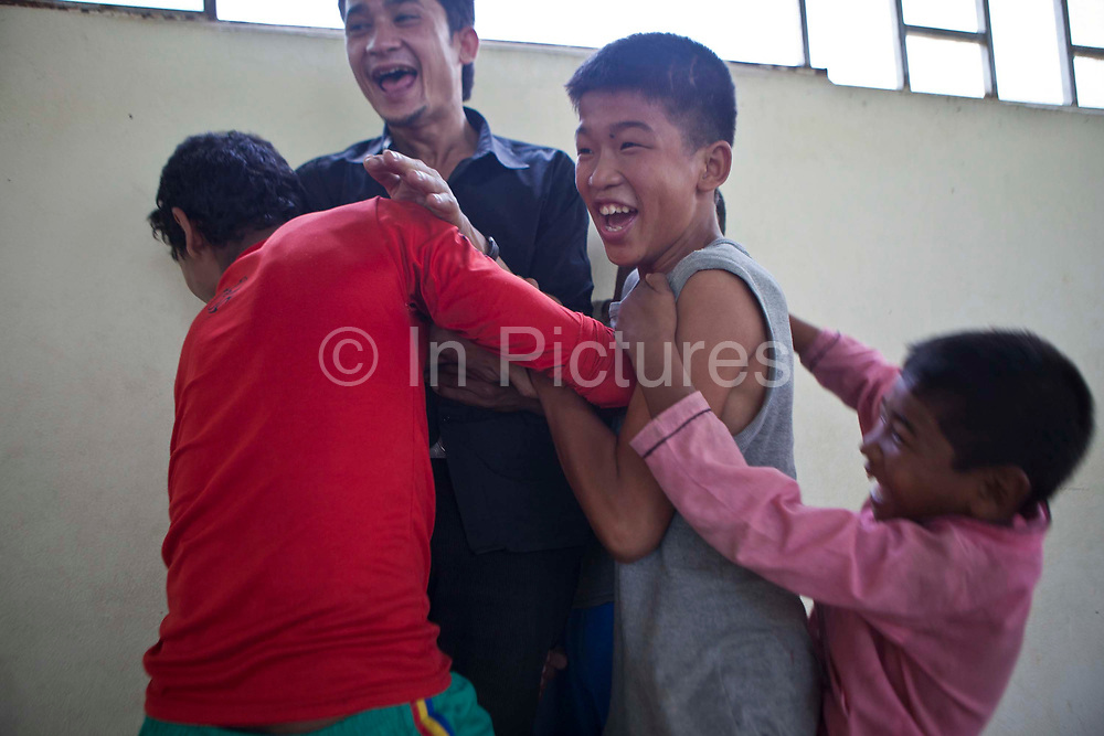 Young Nepalese boys play fight with their carer after a yoga class in the Voice for Children rehabilitation center in Kathmandu, Nepal.  The not-for-profit organisation supports street children and those who are at risk of sexual abuse through educational and vocational training opportunities, health services and psychosocial counseling.  These young children have recently been found by the charity and attend the children's drop-in centre where they play games and activities including yoga classes.