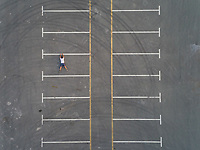 Aerial conceptual view of a man falling from a parking line in Dubai, U.A.E