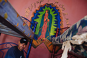Carlos Ortez from El Salvador rests inside a shelter for migrants, after several days traveled through mountains and villages inside Mexico; behind on the wall, a painting of Virgin of Guadalupe in Coatzacoalcos, Mexico, October 6, 2008.