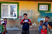 "Adrian (13) posing for a portrait holding an image of himself made about one year before at the Roma settlement ""Budulovska Street"" in Moldava nad Bodvou, Eastern Slovakia about 30 km from Kosice (2014). From about 800 inhabitants of the segregated settlement 'Budulovska Street' (2014) are roughly 392 children up to the age of 16 years."