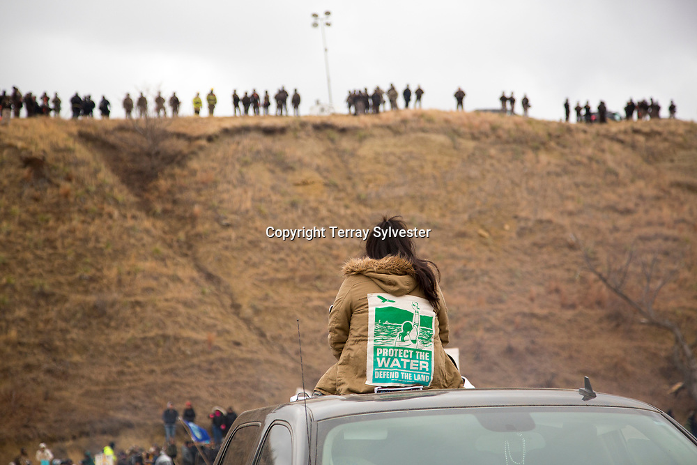 An opponent of the Dakota Access oil pipeline watches police on the hill above her during a prayer ceremony and demonstration near the pipeline route on Thanksgiving Day, November 24, 2016. Cannon Ball, North Dakota, United States.