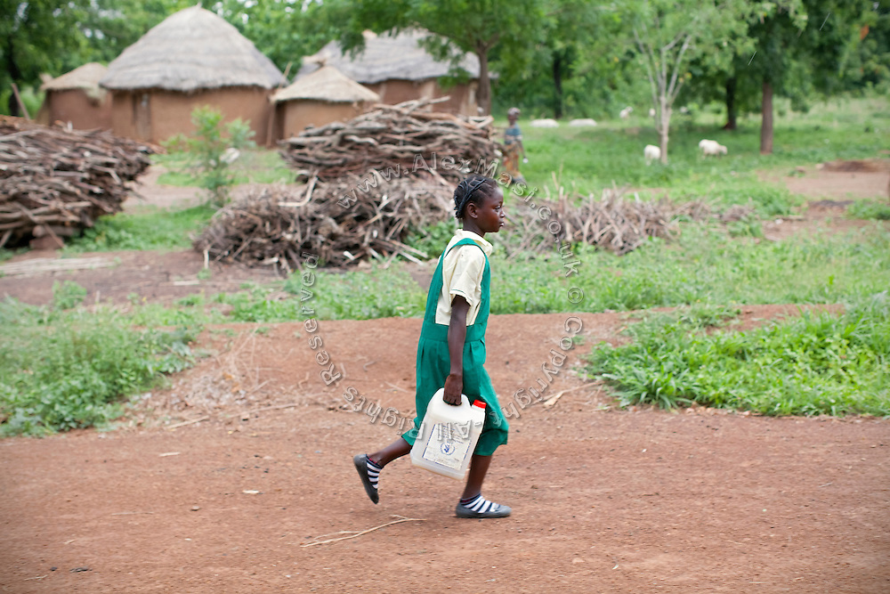 After having collected a load of Shea nuts to help supporting her family, Hassana Ibrahim, 11, is walking back to the village with some water to bring along to her school in Boggu, Tamale, northern Ghana.
