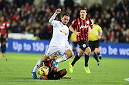 Leon Britton of Swansea city ©  is fouled by Karl Henry  of QPR .Barclays Premier league match, Swansea city v Queens Park Rangers at the Liberty stadium in Swansea, South Wales on Tuesday 2nd December 2014<br /> pic by Andrew Orchard, Andrew Orchard sports photography.