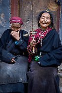 In Tibetan Buddhism, you gain merits by doing certain things. Spinning prayer wheels, praying, hanging prayer flags, and walking koras, all give merits. Tibetans take gaining these merits to extreme degrees. You rarely see an elderly Tibetan ever sitting still. At the very least, they are always spinning a prayer wheel as the woman on the right in this picture.