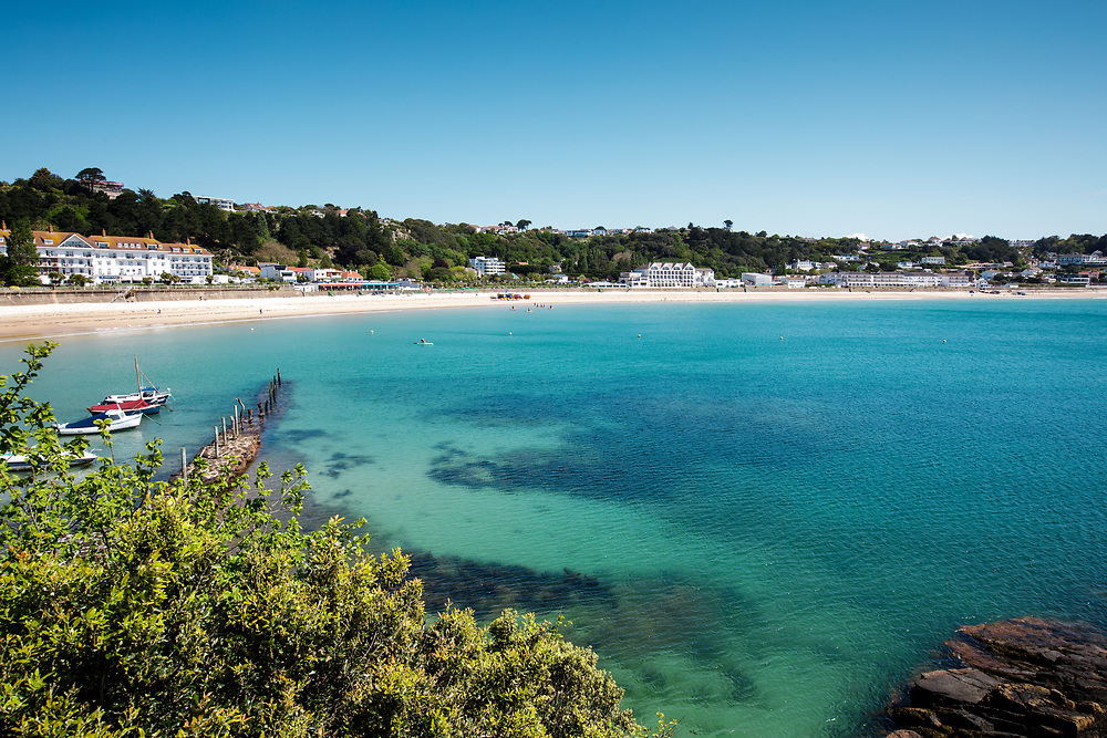 White sand and calm turquoise water at the beach in St Brelade, overlooked by hotel accommodation for the tourism industry in Jersey, Channel Islands