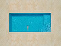 Aerial view of girl diving into swimming pool, Sumartin, Croatia.