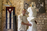 Local Cuban artist in his studio posing for a portrait with his sculptures, Cuban flag in the background, Havana.