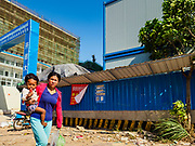 """15 FEBRUARY 2019 - SIHANOUKVILLE, CAMBODIA: A Cambodian woman carries her child past a the construction site of a Chinese casino in Sihanoukville. There are about 80 Chinese casinos and resort hotels open in Sihanoukville and dozens more under construction. The casinos are changing the city, once a sleepy port on Southeast Asia's """"backpacker trail"""" into a booming city. The change is coming with a cost though. Many Cambodian residents of Sihanoukville  have lost their homes to make way for the casinos and the jobs are going to Chinese workers, brought in to build casinos and work in the casinos.    PHOTO BY JACK KURTZ"""