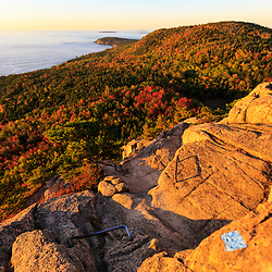 """View of the Atlantic Ocean from the trail on """"The Beehive"""" in fall in Maine's Acadia National Park."""