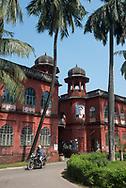 Dhaka, Bangladesh - November 1, 2017: A man on a motorbike drives past a building at the University of Dhaka campus in Bangladesh