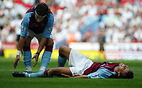 Photograph: Scott Heavey.<br />Aston Villa V Liverpool. FA Barclaycard Premiership match from Villa Park. 24/08/2003.<br />Lee Hendrie lies in agony while Jaun Pablo attempts to help.