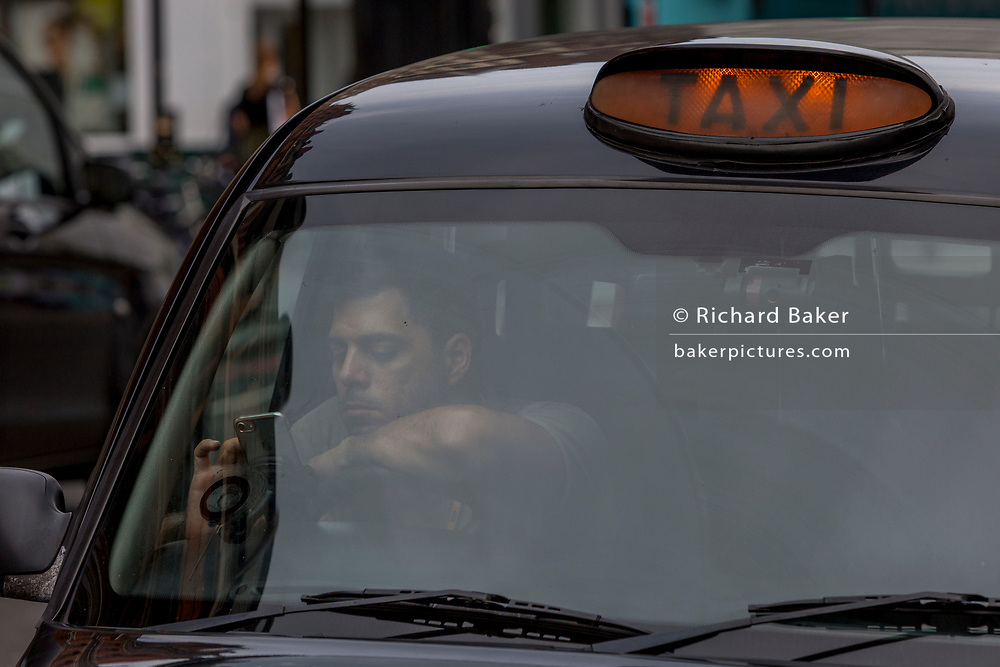 A London cabbie (taxi driver) checks his windscreen-mounted mobile phone while waiting in a queue for fares outside Liverpool Street mainline station in the City of London - the capital's financial district, on 3rd September 2018, in London England.
