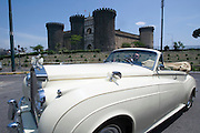 Castel Nuovo. A wedding couple has their photos taken with a Rolls Royce cabriolet.