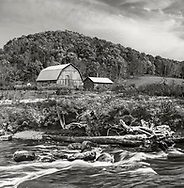 A pastoral scene, barn, pasture and stream flowing through hilly farm land , USA