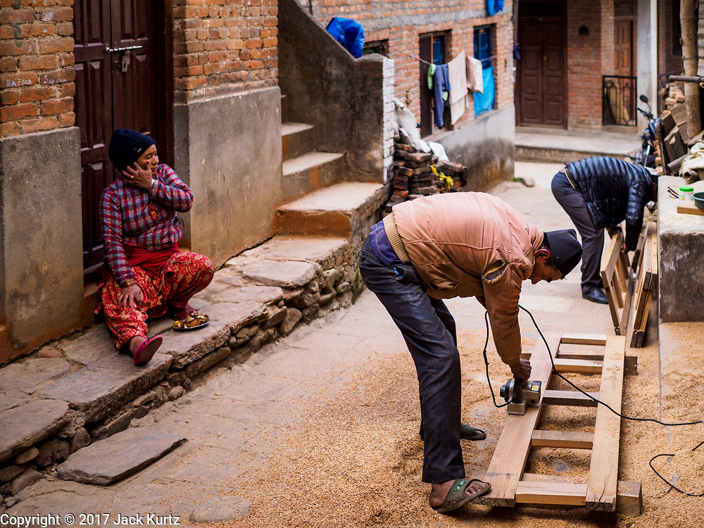 15 MARCH 2017 - BUNGAMATI, NEPAL: Men work on a building frame in a street in Bungamati. Bungamati, a community of wood carvers and artisans, used to be a stop on the tourist trail of the Kathmandu valley but since the 2015 earthquake few tourists visit the community. Recovery seems to have barely begun nearly two years after the earthquake of 25 April 2015 that devastated Nepal. In some villages in the Kathmandu valley workers are working by hand to remove ruble and dig out destroyed buildings. About 9,000 people were killed and another 22,000 injured by the earthquake. The epicenter of the earthquake was east of the Gorka district.            PHOTO BY JACK KURTZ