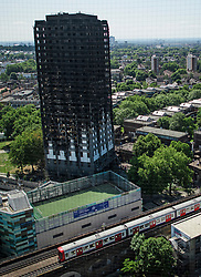 © Licensed to London News Pictures. 17/06/2017. London, UK.  tube train runs in front of Grenfell tower block shortly before nearby Latimer Road station was closed over concerns for the structural safety of Grenfell tower block, following a fire earlier this week. The blaze engulfed the 27-storey building killing 12 - with 34 people still in hospital, 18 of whom are in critical condition. The fire brigade say that they don't expect to find anyone else alive. Photo credit: Ben Cawthra/LNP