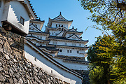 """Himeji Castle is both a national treasure and a UNESCO World Heritage Site, in Hyogo Prefecture, Japan. Unlike many other Japanese castles, it was never destroyed by war, earthquake or fire and survives to this day as one of the country's twelve original castles. History: Starting as forts built in 1333 and 1346, Himeji Castle (aka White Heron Castle or White Egret Castle) was remodeled in 1561, remodeled in 1581, enlarged in 1609 to its present complex, extensively repaired in 1956, and renovated in 2009-15. Displayed inside are historic samurai armour and swords. From the upper floors, view fish-shaped roof ornaments that are believed to protect from fire. Across the moat, visit Koko-en, a pleasing reconstruction of former samurai quarters, nine Edo period homes, plus movie-set gardens. Himeji Castle starred in the 1967 James Bond movie """"You Only Live Twice""""; in Akira Kurosawa's 1980 film """"Kagemusha"""" and 1985 """"Ran""""; and in the 1980 television miniseries Shogun (portraying feudal Osaka castle). By train, Himeji is 3 hours round trip from Kyoto."""