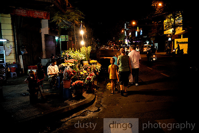 Family group of tourists walking on road at night, past flower seller and his stall. Ho Chi Minh City (Saigon), Vietnam