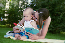Mother and baby boy watching a picture book in lawn, Munich, Bavaria, Germany