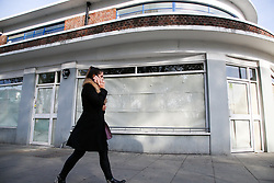 © Licensed to London News Pictures. 19/10/2020. London, UK. A woman in north London walks past a store which has closed due to coronavirus crisis. According to the figures, revealed by the Local Data Company and advisory firm PricewaterhouseCoopers (PwC), a total of 11,120 shops on UK high streets closed in the first half of this year due to the coronavirus lockdown.  Photo credit: Dinendra Haria/LNP