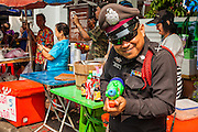 13 APRIL 2014 - BANGKOK, THAILAND:  A Thai police officer shoots a water gun at a tourist on Khao San Road in Bangkok. Songkran is celebrated in Thailand as the traditional New Year's Day from 13 to 16 April. Songkran is in the hottest time of the year in Thailand, at the end of the dry season and provides an excuse for people to cool off in friendly water fights that take place throughout the country. Songkran has been a national holiday since 1940, when Thailand moved the first day of the year to January 1.    PHOTO BY JACK KURTZ