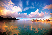 The sun rises above a tropical resort in Tahiti creating bright blues and oranges