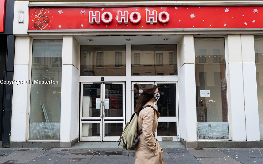 Glasgow, Scotland, UK. 25 November 2020. Glasgow city centre  very quiet during severe level 4 lockdown imposed by the Scottish Government.  Non essential businesses , bars, restaurants and shops are closed. Pictured; Woman walks past empty Christmas store. Credit.  Iain Masterton