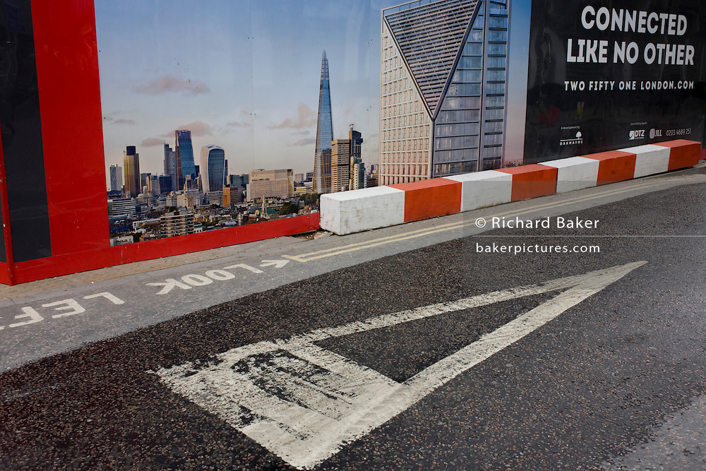 Construction hoarding showing London's Shard skyscraper and Give Way triangle at a road junction in south London.