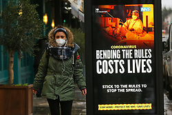 © Licensed to London News Pictures. 20/01/2021. London, UK. A woman wearing a protective face covering walks past the government's 'Don't Help The Virus Spread' publicity campaign poster in north London, after the mutated variant of the SARS-Cov-2 virus continues to spread around the country. On Tuesday 19 January, 1,610 people died in the UK within 28 days of a positive Covid-19 test. This is the biggest figure reported in a single day in the UK since the pandemic began last year. According to government figures over 4.2 million people have now received the first dose of a vaccine. Photo credit: Dinendra Haria/LNP
