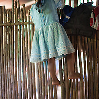 A young girl climbs a wall made of cane in a house in Alta Verapaz