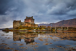 Eilean Donan Castle reflected in the still waters of Loch Duich at dusk with gathering storm clouds above.<br />