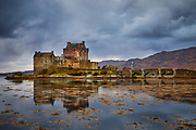 Eilean Donan Castle reflected in the still waters of Loch Duich at dusk with gathering storm clouds above.<br /> Scotland, UK