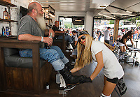 Dave Nelson of Portland, ME gets a boot shine from Aerinn Schlenkov at the Progressive booth and Flo's Chop Shop Thursday afternoon on Lakeside Avenue.  (Karen Bobotas/for the Laconia Daily Sun)