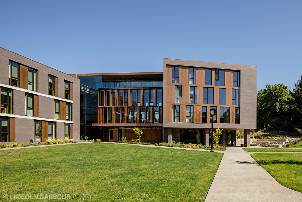 A horizontal view of Trillium Residence Hall showing a manicured lawn in front and blue skies overhead.  The front door is visible.