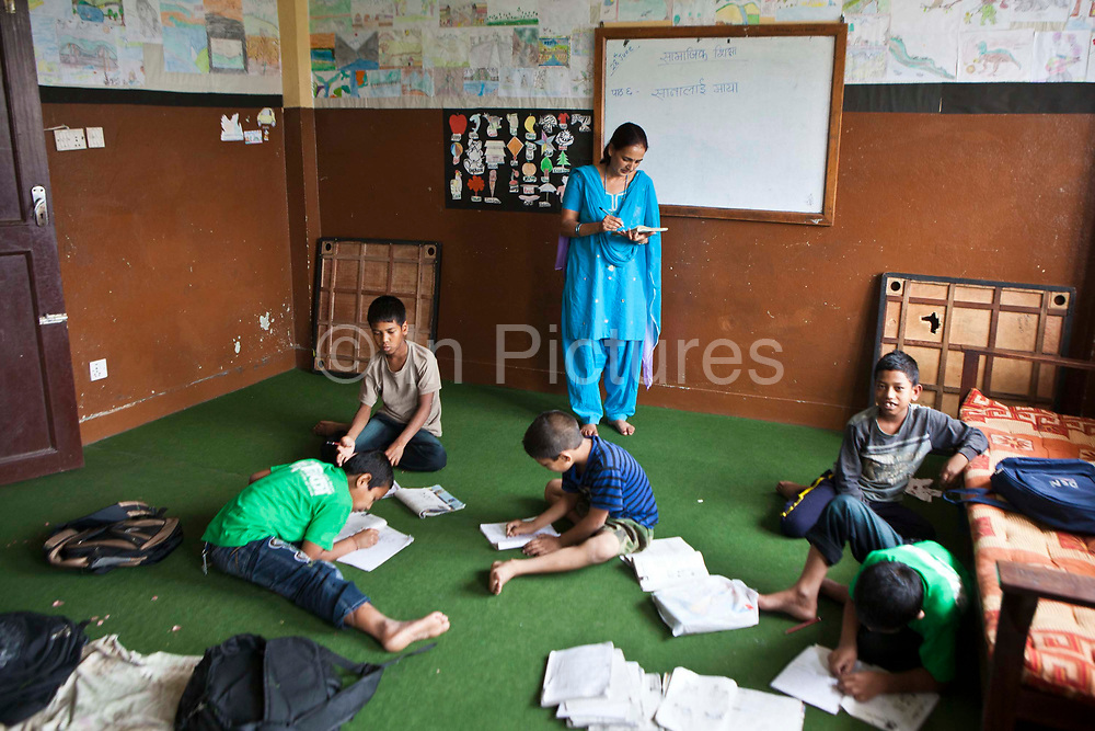 Taria, a Nepalese teacher, looks at her book while her students carry out a writing exercise a class room in the Voice of Children rehabilitation center in Kathmandu, Nepal.  The not-for-profit organisation supports street children and those who are at risk of sexual abuse through educational and vocational training opportunities, health services and psychosocial counseling.