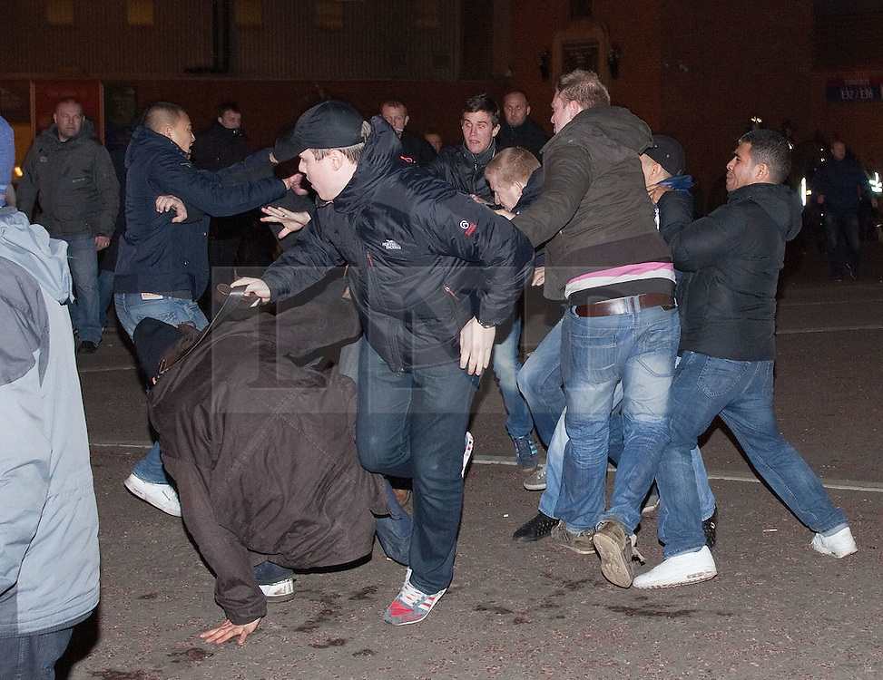 © licensed to London News Pictures. Manchester, UK  23/02/2012. Manchester United and Ajax Amsterdam hooligans fight in front of Old Trafford shortly before kick off of the 2nd leg of the two teams' Europa League tie at Old Trafford. Photo credit should read Joel Goodman/LNP