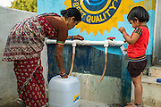 A child waits as her mother buys safe water from the iJal station in Peddapur, a remote village in Warangal, Telangana, India, on 22nd March 2015. Safe Water Network works with local communities that live beyond the water pipeline to establish sustainable and reliable water treatment stations within their villages to provide potable and safe water to the communities at a nominal cost. Photo by Suzanne Lee/Panos Pictures for Safe Water Network