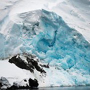 """A wall of blue glacier ice slowly flows over rocks to the sea on the side of the mountains at the Lemaire Channel in Antarctica. The Lemaire Channel is sometimes referred to as """"Kodak Gap"""" in a nod to its famously scenic views."""
