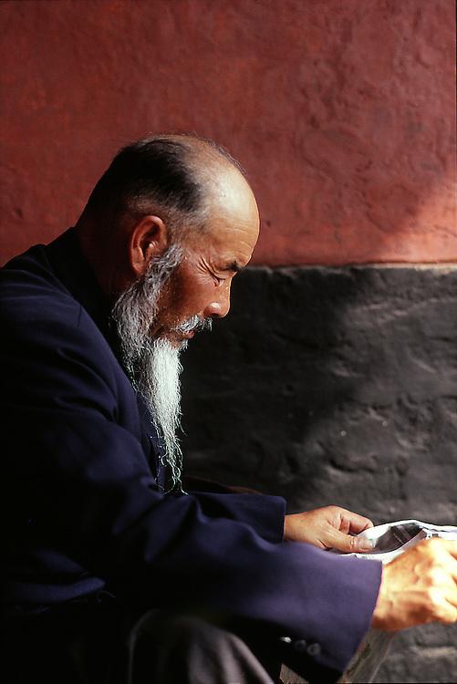 Master Gu reading the morning news in Guangzhou, China.